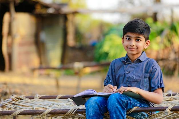自宅で彼の宿題をしているインドの子