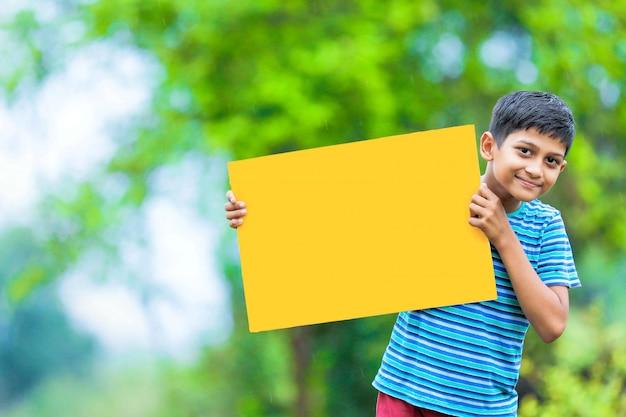 Индийский ребенок держит пустой плакат