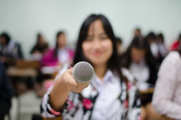 Микрофон в руке женщины в зале заседаний