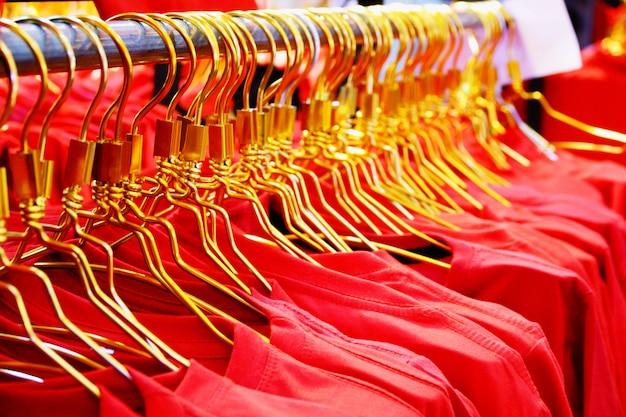 ショッピングモールのラックに赤いシャツを着た