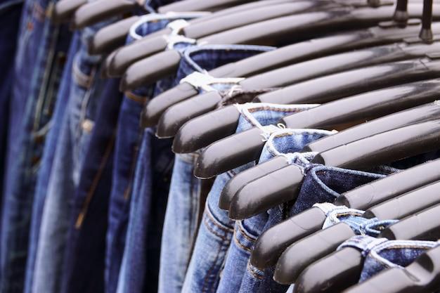 Закрыть много джинсов, висящих на стойке