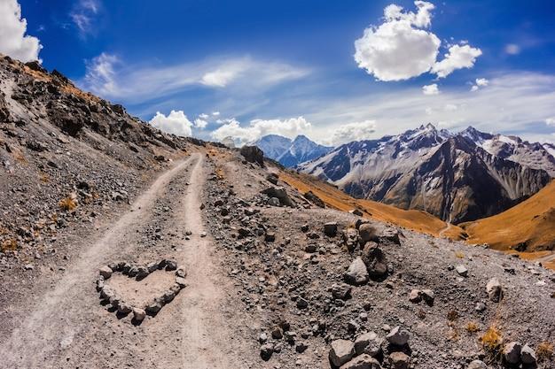 Главный кавказский хребет с горы эльбрус с сердцем из камней на переднем плане
