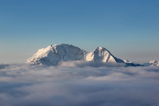 雲の上にそびえ立つコーカサス山脈の山頂のパノラマ