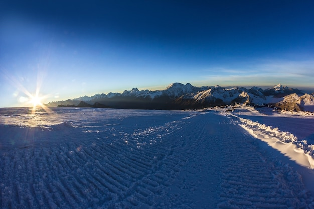 Широкая дорога от снежной кошки и горного хребта в лучах восходящего солнца