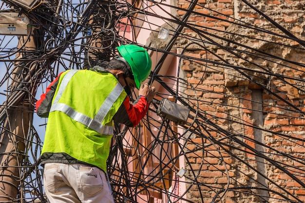 Рабочий фиксирует электрические провода на столбе снаружи