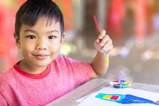 部屋の紙にアジアの学生が絵を描いて絵を描く。