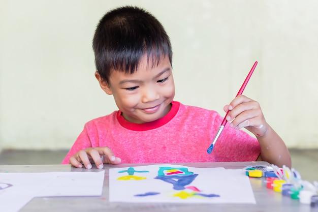 部屋の紙にアジアの学生が絵を描いて色を塗る。