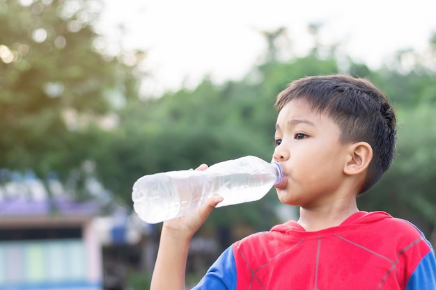 ペットボトルで水を飲んで幸せなアジアの子供学生少年。運動終了後。