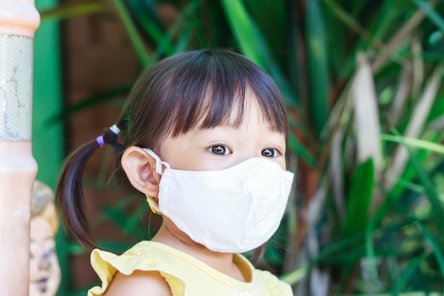 笑顔と布マスクを身に着けているアジアの子供女の子、