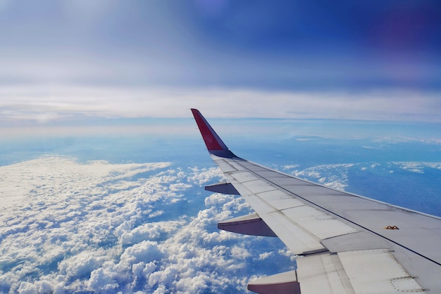 座席内の飛行機の窓からの航空機の翼の眺め。