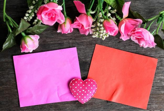 バレンタインコンセプト、木製の背景にバラの花とピンクと赤の紙のモックアップ。