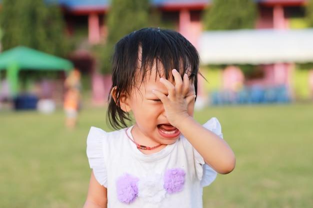 彼女は遊び場でおもちゃで遊んで泣いているアジアの子女の子。