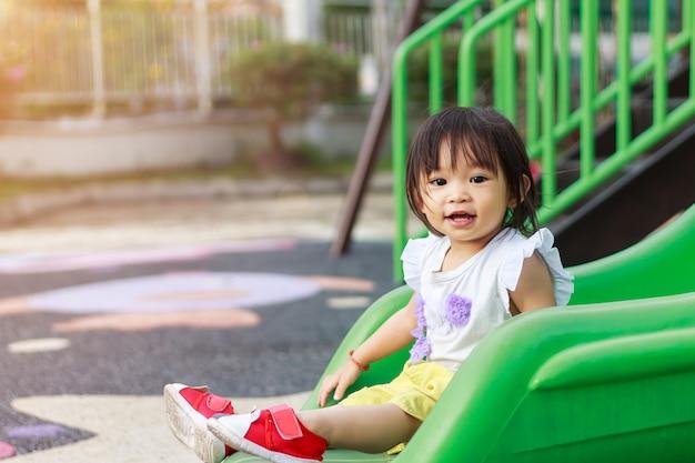 Счастливый азиатский ребенок девочка улыбается и смеется. она играет с игрушкой-слайдером на детской площадке.