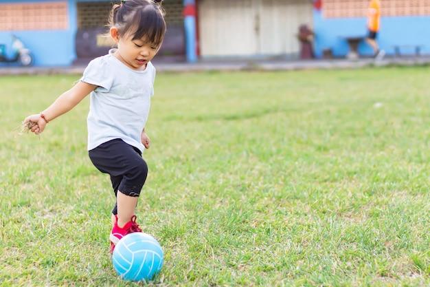 Счастливая азиатская девушка ребенка младенца играя и пиная шарик забавляется на спортивной площадке поля.