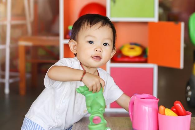 Счастливая азиатская девушка ребенка усмехаясь и играя с много игрушек на комнате.