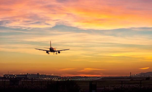 美しい夕日の光の中で空港の滑走路に着陸する乗客の飛行機