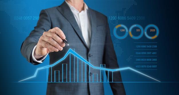ビジネスマンは、グラフに鉛筆で経済成長の傾向をマークします
