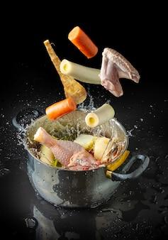 水しぶきで鍋に向かって飛んでいるスープを作るための材料