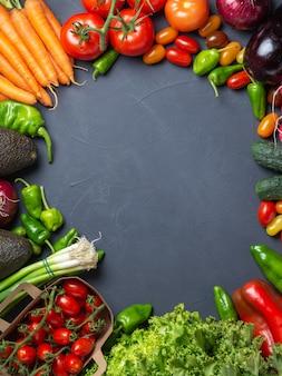 コピースペースの暗い木製の背景-画像の中心にサークルと新鮮な野菜