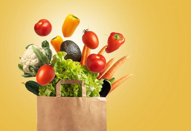 黄色の背景、コピースペースに野菜でいっぱいの環境に優しい再利用可能なショッピングバッグ