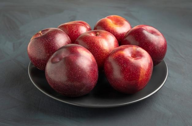 素朴なテーブルに新鮮な季節のプルーンとプレート