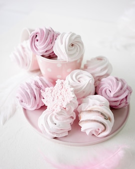 Розовые и белые безе на белом фоне. чашка на горошек