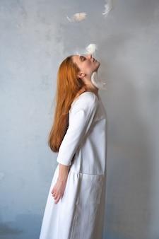 Ян женщины в белом платье и летающие белые перья