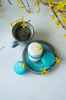 白と青緑色のマカロンと白い背景の上のコーヒーカップ。春の黄色い花