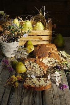 レーズンと素朴なスタイルの木製のテーブルの上の梨のケーキ