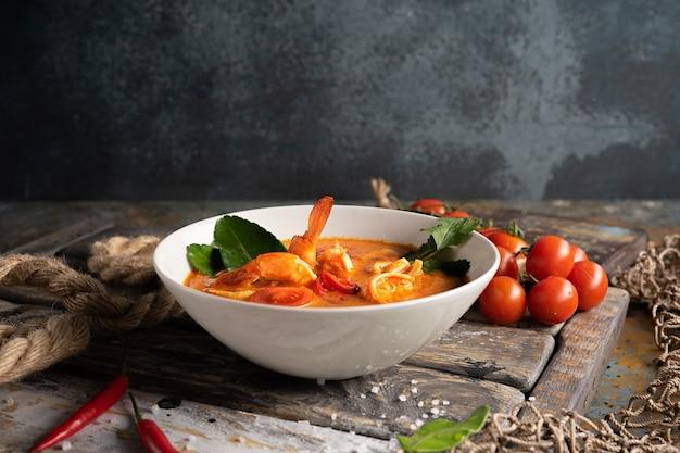 Суп том ям с креветками, кальмарами и острым перцем на текстурированной деревянной доске