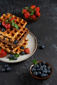 セラミックプレートに新鮮な果実とチョコレートとバニラのベルギーワッフル