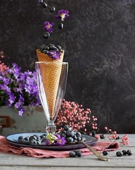 Ягоды черники в вафельном стаканчике в окружении фиолетовых цветов и ягод. летняя тема. левитация