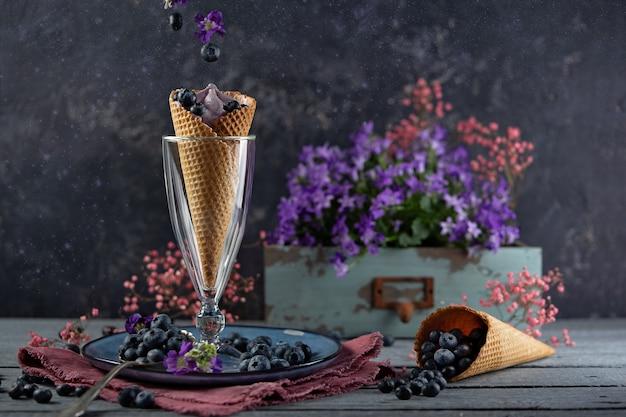 紫色の花と果実に囲まれたワッフルカップのブルーベリー果実。夏のテーマ浮上