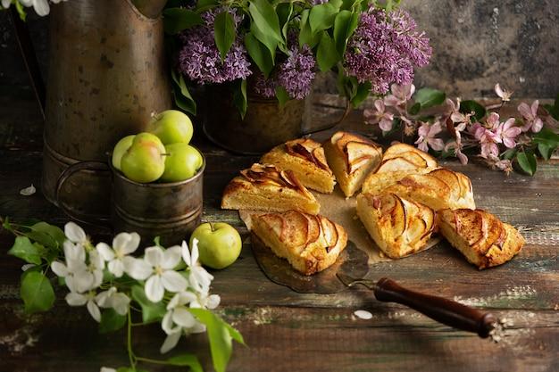 Домашние яблочные булочки с корицей с цветами сирени и веток яблони. английский завтрак или поздний завтрак в деревне