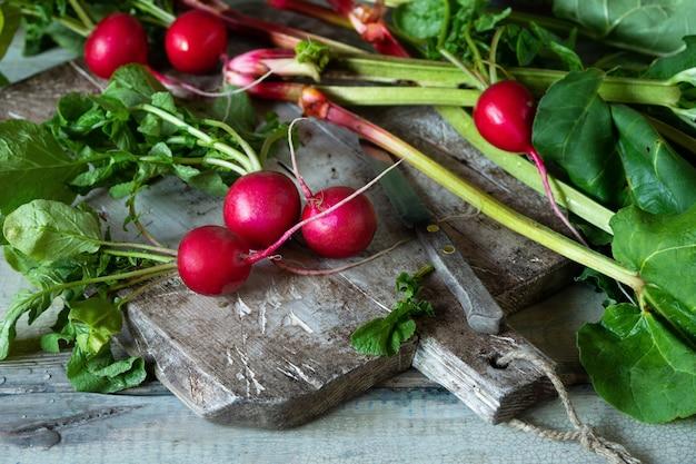 Молодая свежая редька на старинной разделочной доске на зеленый. стебли ревеня и редис с листьями. сбор свежих овощей