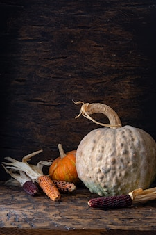 カボチャと古い木製のテーブルにトウモロコシの秋の静物。