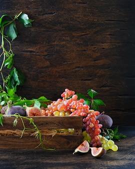 赤と緑のブドウと古い木の板のデカンタで白ワインの熟した束