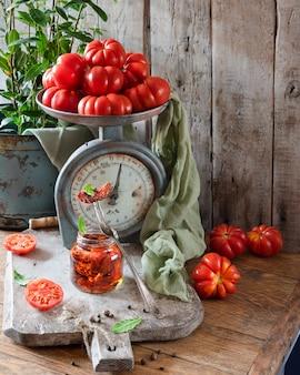 木製のまな板の上のガラスの瓶に天日干しトマト。