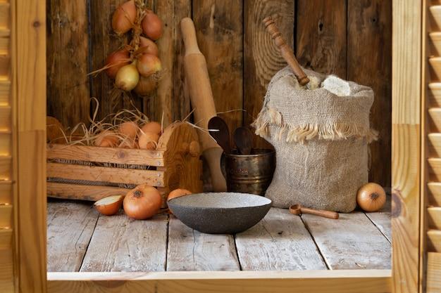 木製のテーブルに素朴な静物、小麦粉、玉ねぎ、卵、スパイス。