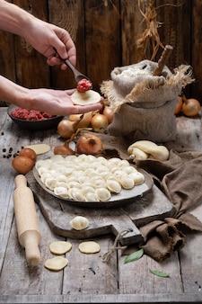 調理肉団子-まな板と食材にロシアのペリメニ
