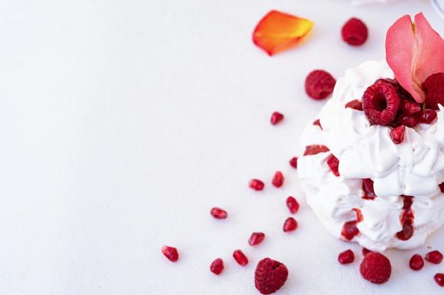 ラズベリーとバラの花びらと白い背景のザクロの種子とパブロワケーキ