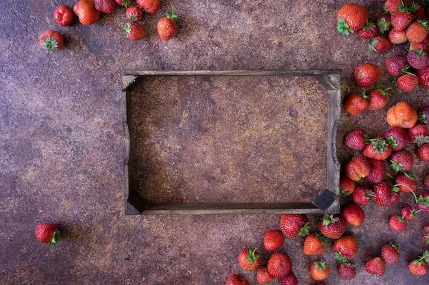 Клубника на коричневой предпосылке, взгляд сверху. каркас из свежей клубники и деревянной коробки