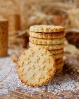 木製の背景に蝶のプリントでクッキーを切る