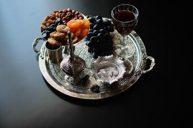 赤ワイン、クルミ、ブドウ、暗い背景にイチジクのワイングラス