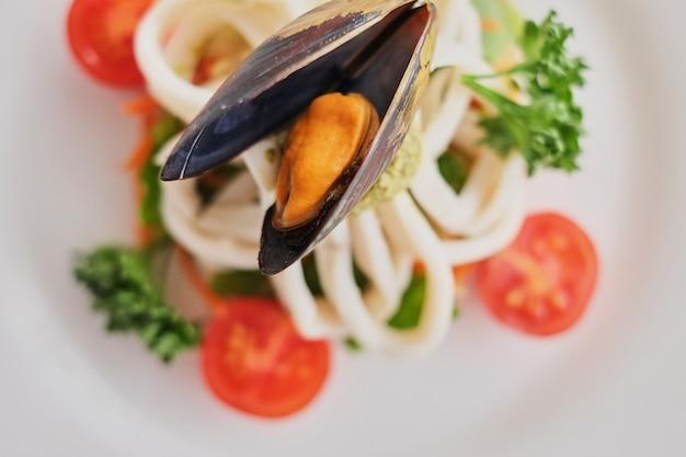 イカとムール貝の白い背景の上の白い皿の上の野菜