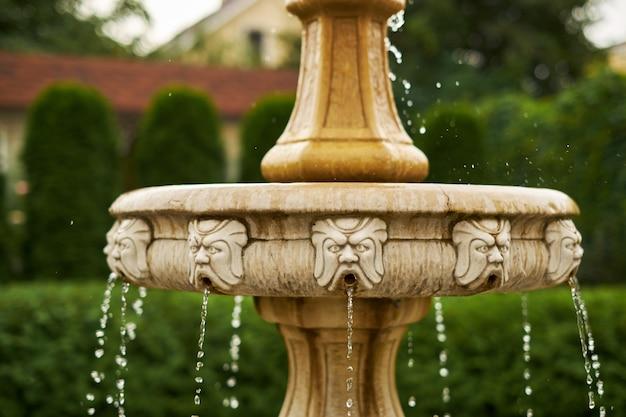 Античный маленький водопад в саду падают капли