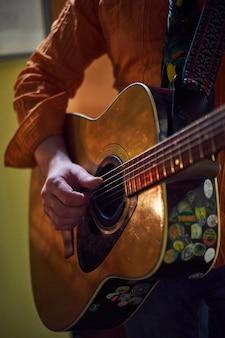 実生活で遊んでいます。ギターを弾くと改善男性の強い手のクローズアップ
