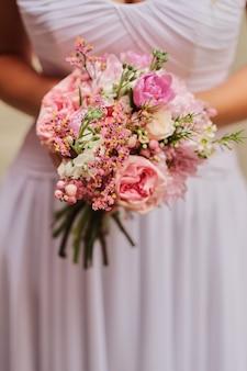パステルカラーのピンク色のウェディングブーケを持って花嫁。