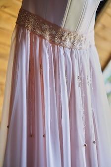木製の覆いのフックにウェディングドレス