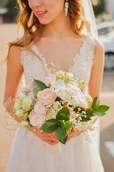 パステル調のピンク色のウェディングファインアートブーケを持つ花嫁。閉じる。